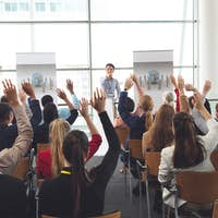 Diverse business people raising hands at business seminar
