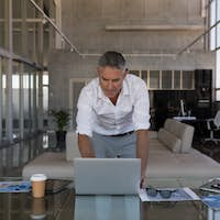 Front view of middle-aged Caucasian male executive concentrating while using laptop in modern office