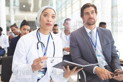 Female doctor with  businessman attending seminar in office. She holding a notebook