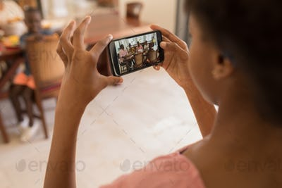 Girl taking a photo of her family sitting at the dining table with her mobile phone at home
