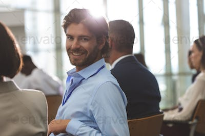 Portrait of happy young Caucasian businessman looking at camera during seminar in office building
