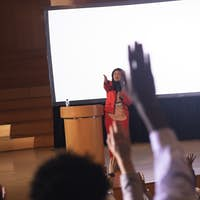 Businesswoman listening and asking while audience raising hand for the queries in the auditorium
