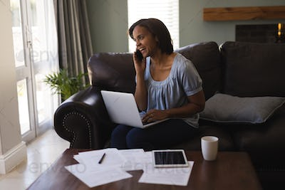 Front view of woman talking on mobile phone while using laptop in living room at home