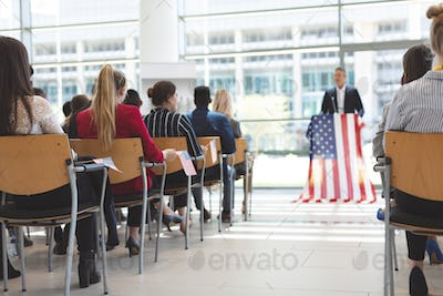 Businessman speaks at a business seminar in office building with american flag