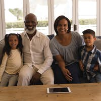 Front view of a multi-generation African American family sitting on sofa in living room at home