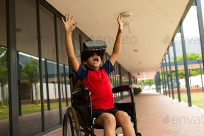 Disabled schoolboy using virtual reality headset with his hands in the air in corridor at school