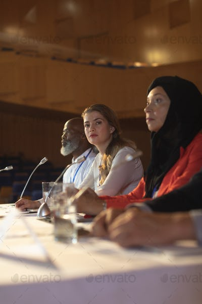 Businesswoman looking at camera while business colleague sitting together in the auditorium