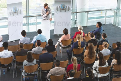 Businessman with microphone speaking in front of business people at business seminar in office