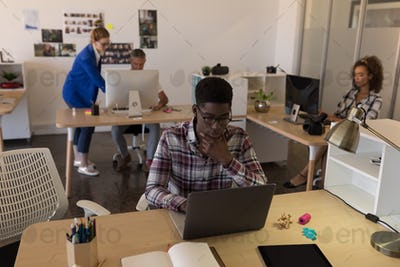 Side view of young African-American male executive working on laptop at desk in the modern office