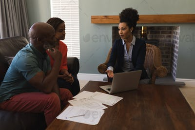 Female real estate agent and senior couple discussing over laptop at home