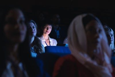 Businesswoman holding laptop and listening to the presentation in auditorium