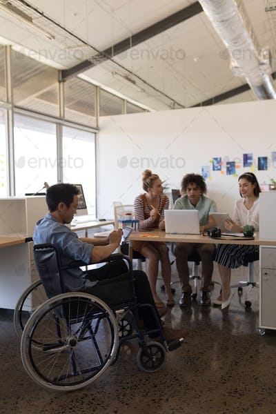 Disabled male executive using digital tablet at office