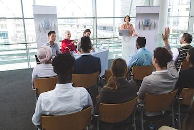 Businesswoman raising hand in business seminar in office building