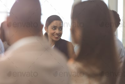 Businesswoman interacting with her colleague during seminar in office building
