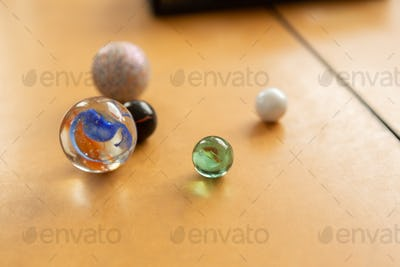 Close-up of beautiful marbles on a wooden desk in classroom at school
