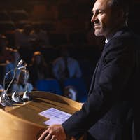 Side view of Caucasian businessman standing on a stage of auditorium for presentation