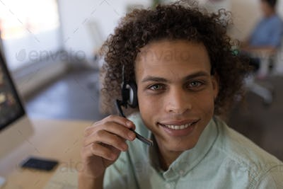Portrait of handsome mixed race male executive in headset sitting at desk in office