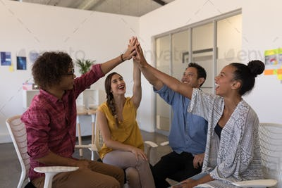 Business colleagues giving high five to each other after successful meeting in modern office