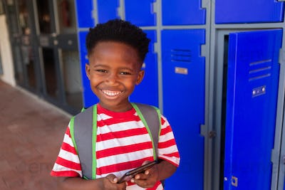 Front view of a smiling African American schoolboy holding mobile phone in the locker room at school