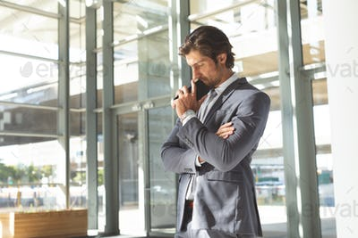 Businessman with head down on his mobile phone standing in lobby