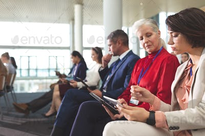 Businesswomen discussing over digital tablet during business seminar in office building