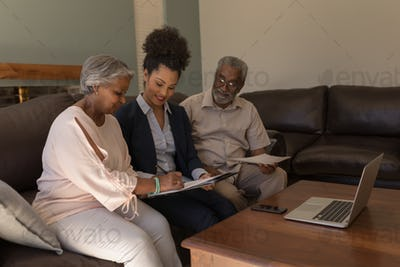 Woman signing property contract with real estate agent and senior man in living room at home