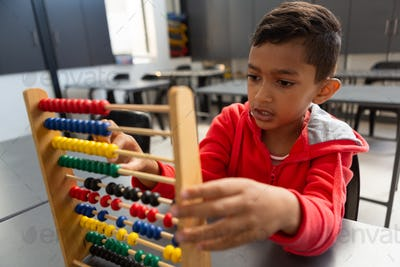 Schoolboy learning math with abacus at desk in classroom at elementary school