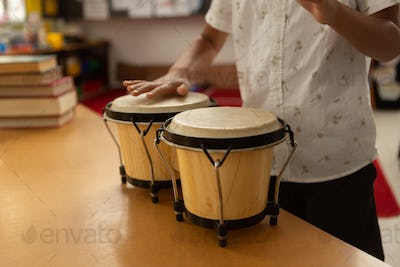Mid section of cute mixed-race schoolboy playing bongo in a classroom at elementary school