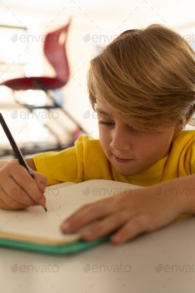 Front view of Caucasian boy drawing sketch on notebook at desk in a classroom at elementary school