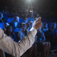 Rear view of Caucasian businessman giving presentation in front of audience in auditorium