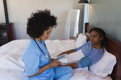 Female doctor measuring blood pressure with sphygomanometer of senior woman at home