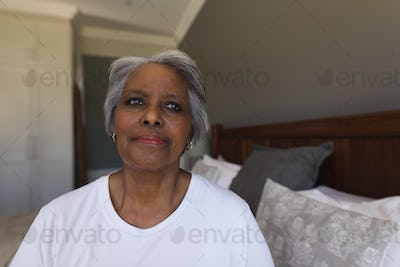Portrait of a thoughtful senior African American woman sitting on her bed at home
