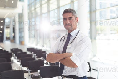 Side view of Caucasian male doctor with arms crossed looking at camera in a conference room