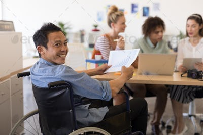 Portrait of disabled Asian male executive holding paper with graph in modern office