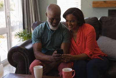 Front view of active senior couple using mobile phone in living room at home