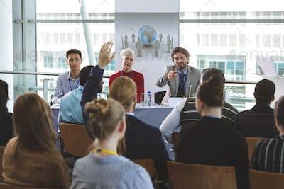 Businessman raising handat business seminar in office building