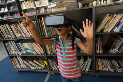 Front view of playful mixed-race schoolgirl using virtual reality headset in the library at school