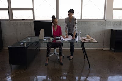 Female executives discussing over blueprint at desk in modern office