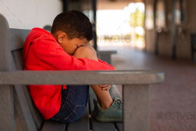 Side view of sad mixed-race schoolboy sitting alone on bench in corridor at elementary school