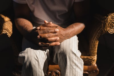 Mid section of senior African American man siting on wicker chair with hands clasped at home