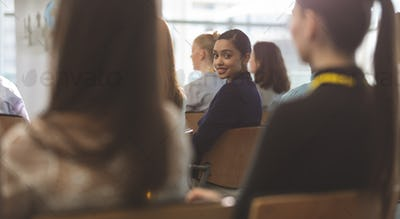 Businesswoman looking at camera during seminar in office building
