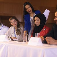 Front view of young mixed race businesswoman showing documents to the panel of speaker