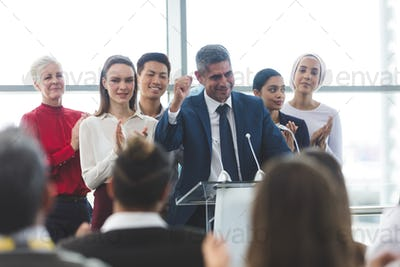 Businessman standing with diverse colleagues while speaking at business seminar in office building