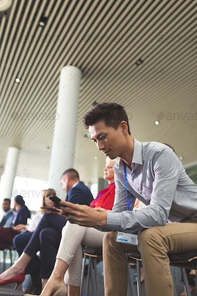 Businessman using mobile phone during business seminar in office building