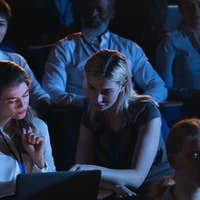 High angle view of Caucasian businesswoman sitting and discussing over the laptop in the auditorium