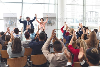Diverse business people applauding and celebrating at business seminar in office building