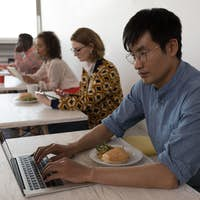 Side view of young diverse business colleagues using electronic devices in modern office