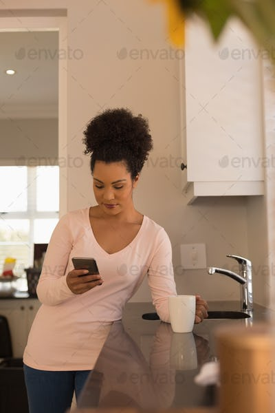 Beautiful woman having coffee while using mobile phone in kitchen at home