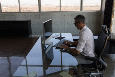 Side view of middle-aged Caucasian male executive working hard on computer at desk in modern office