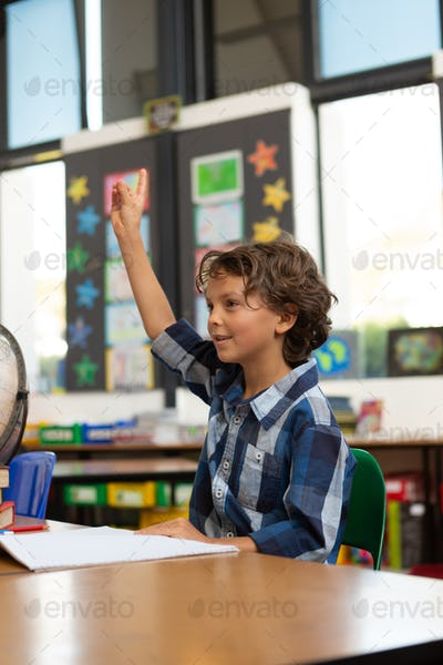 Side view of a Caucasian schoolboy raising his hand while sitting at desk in the classroom at school